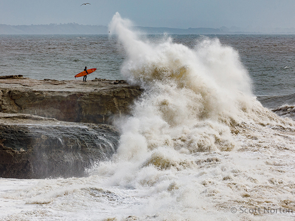 surfer standing on rock in santa cruz as large wave crashes by scott norton